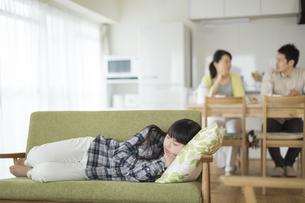 ソファーで横になって昼寝をする女の子の写真素材 [FYI01624113]