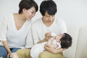 赤ちゃんにミルクを飲ませる両親の写真素材 [FYI01624124]