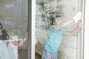 窓拭きをする兄と妹の写真素材 [FYI01624132]