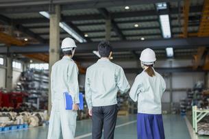 工場で立つ男女作業員の後姿の写真素材 [FYI01624133]