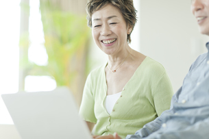ソファーでパソコン操作をする中高年夫婦の写真素材 [FYI01624147]