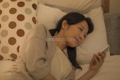 ベットに寝転んでスマートフォンを見る女性の写真素材 [FYI01624148]