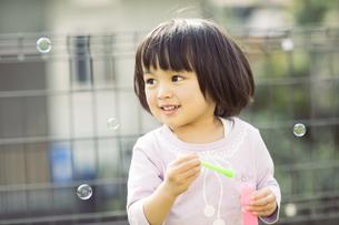 シャボン玉で遊ぶ女の子の写真素材 [FYI01624152]