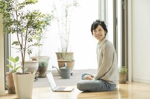 窓辺に座る笑顔の女性の写真素材 [FYI01624153]