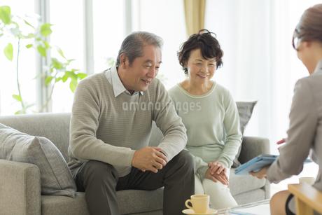 商談をするシニア夫婦とビジネスウーマンの写真素材 [FYI01624157]