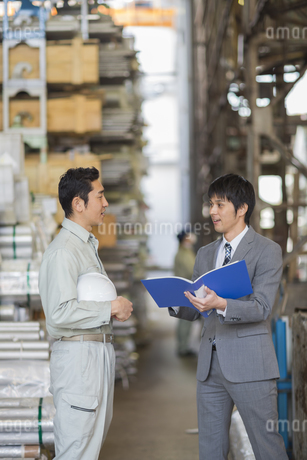 倉庫で打ち合わせをする男性社員の写真素材 [FYI01624160]