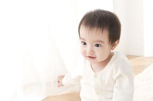 カーテンで遊ぶ赤ちゃんの写真素材 [FYI01624166]