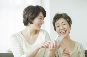 スマートフォンを持って笑顔の母と娘の写真素材 [FYI01624174]
