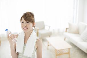 ペットボトルの水を持って笑顔の女性の写真素材 [FYI01624177]