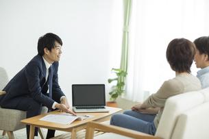 夫婦に説明をするビジネスマンの写真素材 [FYI01624185]