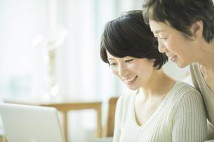ノートパソコンのモニタを見る母と娘の写真素材 [FYI01624191]