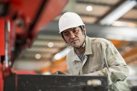 機械を操作する作業服の男性の写真素材 [FYI01624195]