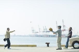 海岸でキャッチボールをするシニア男性の写真素材 [FYI01624199]