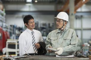 打ち合わせをする作業員とビジネスマンの写真素材 [FYI01624200]