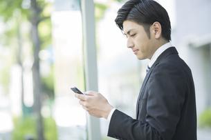 携帯電話を見るビジネスマンの写真素材 [FYI01624228]