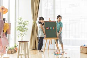 アルファベットを並べた黒板の横に立つ兄と妹の写真素材 [FYI01624237]