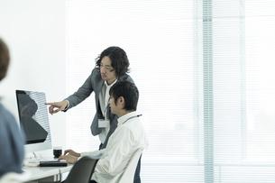 パソコンのモニターを見ながら打ち合わせをするビジネスマンの写真素材 [FYI01624242]
