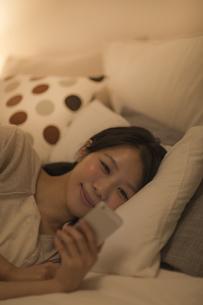ベットに寝転んでスマートフォンを見る女性の写真素材 [FYI01624246]