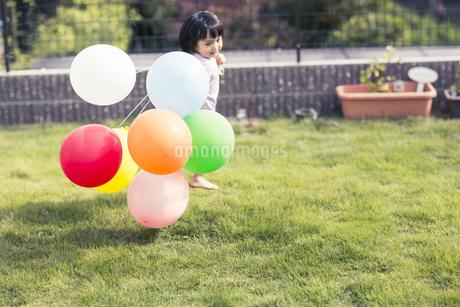 風船を持って走る女の子の写真素材 [FYI01624256]