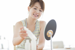 化粧品を取る若い女性の写真素材 [FYI01624264]