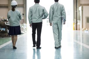 工場で歩く男女作業員の後姿の写真素材 [FYI01624271]