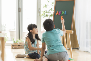 アルファベットで遊ぶ兄と妹の写真素材 [FYI01624274]
