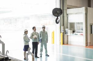 工場で上を見上げる男女の作業員の写真素材 [FYI01624276]
