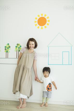 壁のイラストの前に立つ親子の写真素材 [FYI01624280]