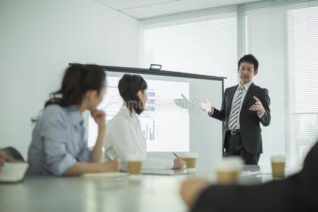 プロジェクターを使用した会議で説明をするビジネスマンの写真素材 [FYI01624291]
