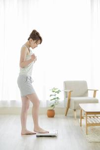 体重計に乗る若い女性の写真素材 [FYI01624304]