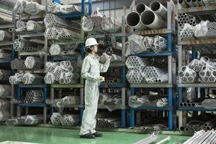 倉庫で働く作業服の男性の写真素材 [FYI01624306]
