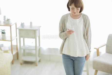 スマートフォンを見る若い女性の写真素材 [FYI01624309]