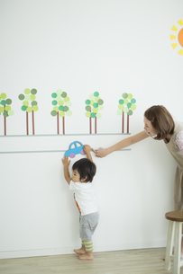 壁のイラストの前で遊ぶ親子の写真素材 [FYI01624317]