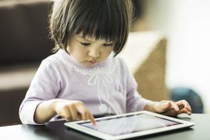 タブレットPCで遊ぶ女の子の写真素材 [FYI01624323]