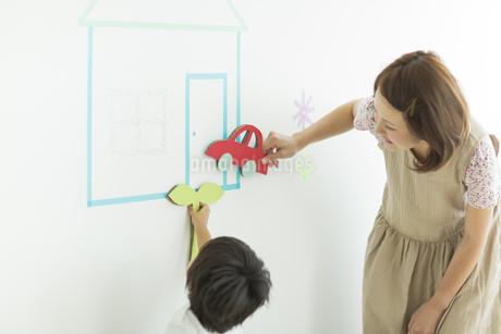 壁のイラストで遊ぶ親子の写真素材 [FYI01624324]