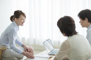 夫婦に商談をするビジネスウーマンの写真素材 [FYI01624329]