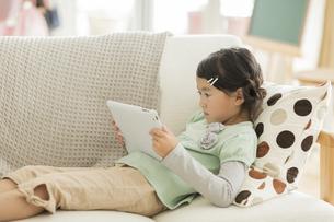 ソファーでタブレットPCを見る女の子の写真素材 [FYI01624344]