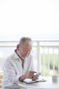 バルコニーでスマートフォンを操作するシニア男性の写真素材 [FYI01624358]