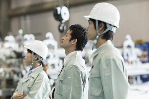 工場で上を見上げる男女の作業員の写真素材 [FYI01624360]