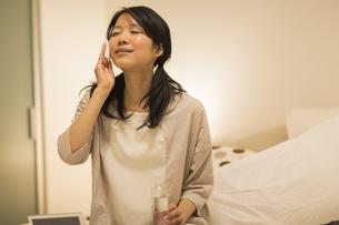 ベッドの上でスキンケアをする女性の写真素材 [FYI01624362]
