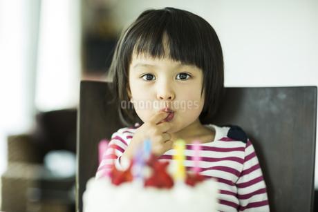 ケーキのクリームを舐める女の子の写真素材 [FYI01624372]