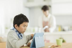 テーブルでタブレットPCを見る男の子の写真素材 [FYI01624376]