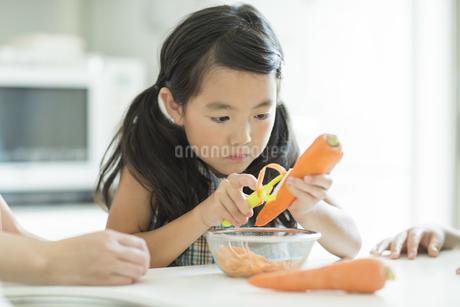 にんじんの皮を剥く女の子の写真素材 [FYI01624380]