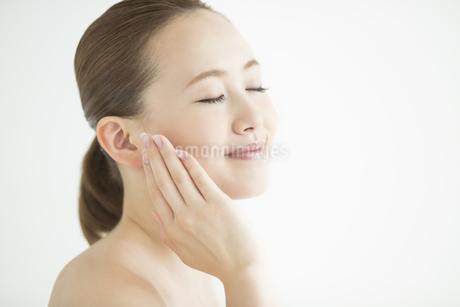 頬に手をあてる女性のスキンケアイメージの写真素材 [FYI01624382]