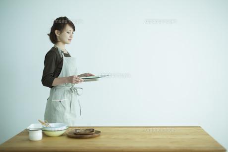 食器を運ぶ女性の写真素材 [FYI01624384]