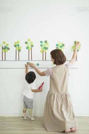 壁に紙を貼る親子の写真素材 [FYI01624398]