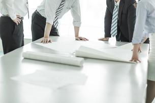 テーブルに図面を広げて打ち合わせをするビジネスマンとビジネスウーマンの写真素材 [FYI01624405]