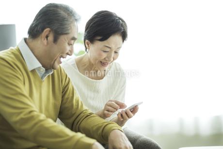 スマートフォンを見るシニア夫婦の写真素材 [FYI01624409]