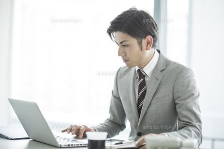 デスクに座ってパソコンをするビジネスマンの写真素材 [FYI01624414]