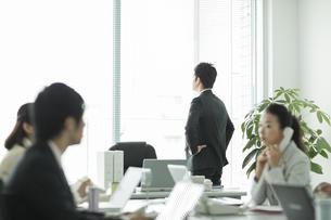 窓辺に立ち外を見るビジネスマンの写真素材 [FYI01624415]